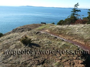 The trail above Juniper Point reveals glaciated serpentinite. Weathering produces distinctive red soils.