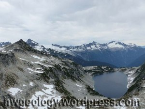 View east from the saddle. Hidden Lake below in its granodiorite-lined cirque. Peaks: near left: north Hidden Lakes Pk; the dark tower of Eldorado is just behind. Above the lake is the dark pyramid of Forbidden Peak; to the right, the Boston-Sahale group above the deep hole of the upper Cascade River.